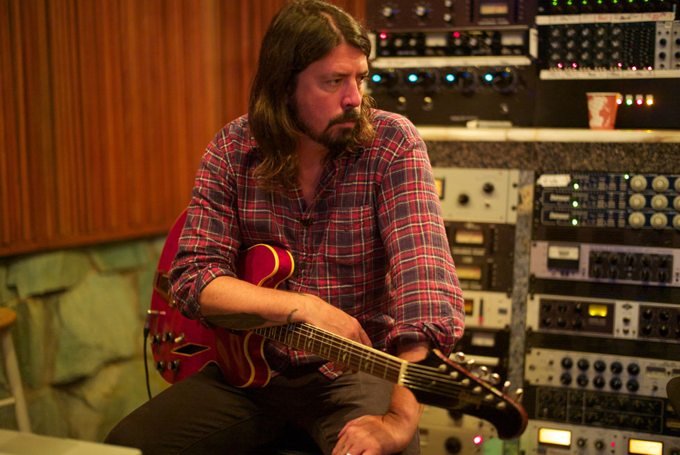Dave Grohl with guitar in studio. Photographer: Andrew Stuart