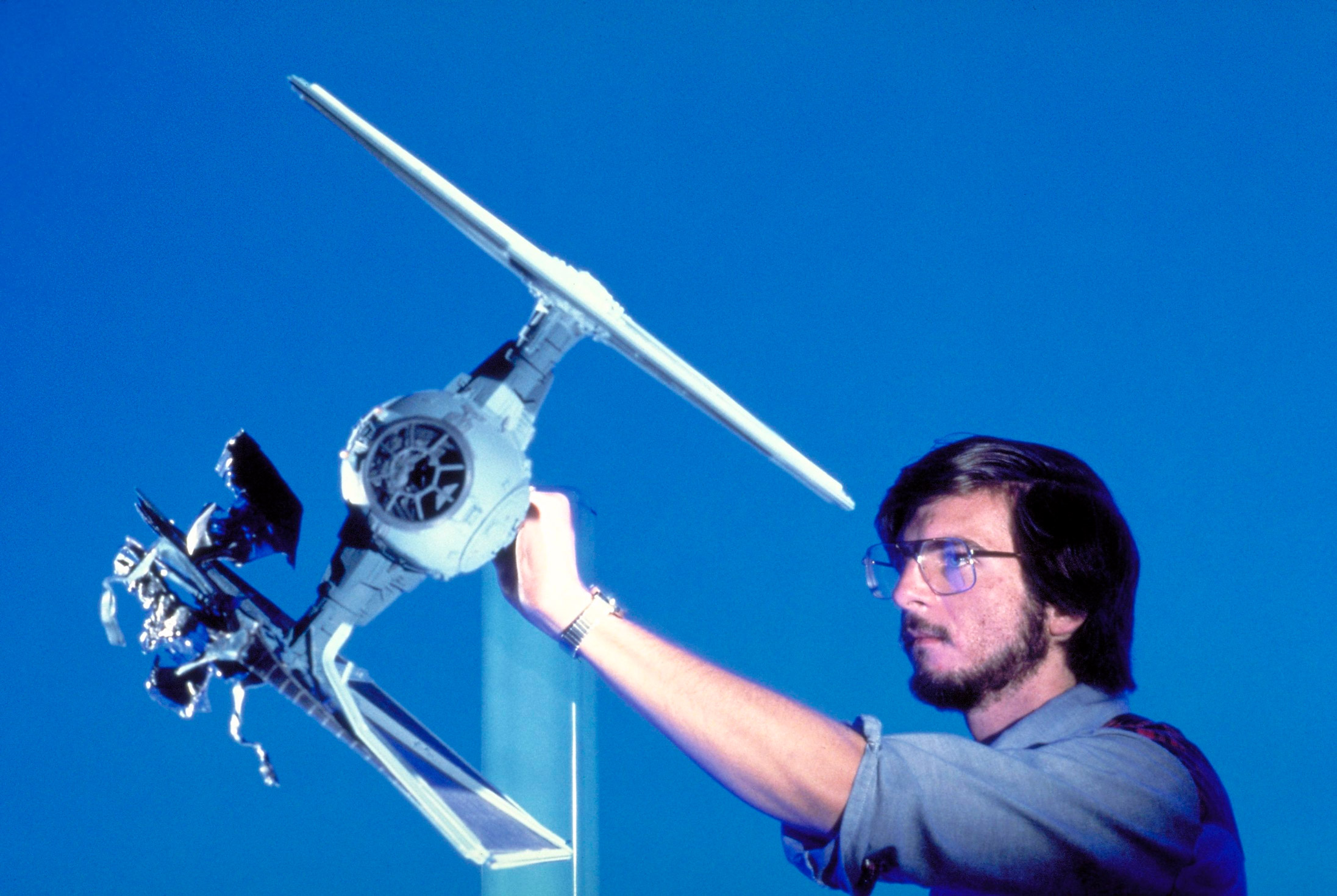 Ken Ralston adjusts a damaged TIE fighter on set (image: LucasFilm).